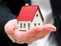 En fastighetsmäklare som rymmer ett litet nytt hus i henne händer Royaltyfri Bild