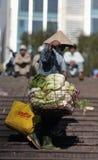 En fattig kvinna i upptagen marknad i Vietnam Arkivbild