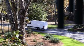 En Fedex, Ups eller den Usps leveranslastbilen som gör en leverans Royaltyfri Fotografi