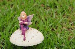 En felik statyett på en champinjon i trädgården Arkivfoton
