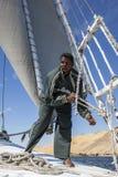 En feluccajungman justerar seglar stund som seglar ner flodNilen i Egypten Arkivbilder