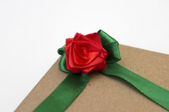En feriegåva som slås in i pappers- och binds med ett grönt band med en röd rosblomma Royaltyfri Foto
