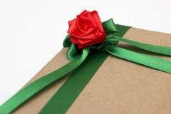 En feriegåva som slås in i pappers- och binds med ett grönt band med en röd rosblomma Royaltyfri Fotografi