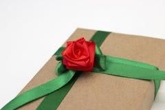 En feriegåva som sloggs in i pappers- och bands med ett grönt band med en röd blomma, steg Royaltyfri Foto
