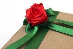 En feriegåva som sloggs in i pappers- och bands med ett grönt band med en röd blomma, steg Fotografering för Bildbyråer