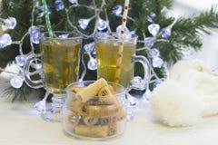 En festlig stilleben med två kopp te och en bunke av kakor vid en julgran med felika ljus Fotografering för Bildbyråer