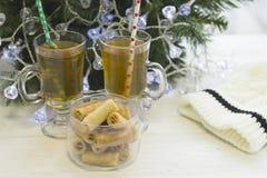 En festlig stilleben med två kopp te och en bunke av kakor vid en julgran med felika ljus Royaltyfri Fotografi