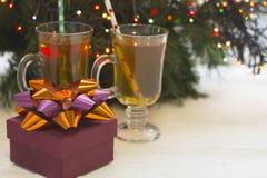 En festlig stilleben med två kopp te och en gåvaask vid en julgran med felika ljus Royaltyfria Bilder