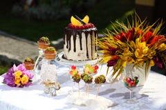 En festlig tabell dekorerade med födelsedagkakan med blommor och sötsaker Royaltyfria Foton