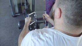 En fet caucasian man utarbetar i idrottshallen på den Hamer simulatorn med hjälpen av en härlig flickas individuella instruktör arkivfilmer