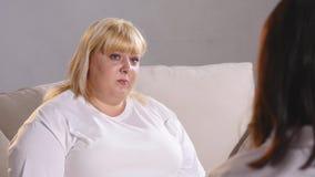 En fet kvinna klagar till en dietist om hennes diagram Fet kvinnagråt arkivfilmer