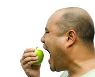 En fet man är att tvinga som är självt att äta ett äpple Arkivbild