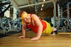 En fet man gör push-UPS från golvet i idrottshallen arkivfoton