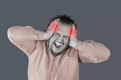 En fet man har hög blodtryck och huvudvärk Övervikt och hälsoproblem royaltyfri foto