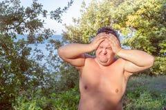 En fet man har hög blodtryck och huvudvärk Övervikt och hälsoproblem royaltyfri fotografi