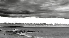 En filt av dramatiska moln täcker himlen som brygder för en storm längs horisonten, i svart & vitt arkivfoton