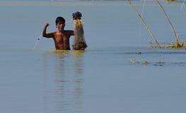 En fiskare är upptagen, i att gjuta hans fisknät och metspön bara i floden royaltyfri fotografi