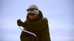 En fiskare borrar ett hål med en gul is borrar in vintern på floden stock video