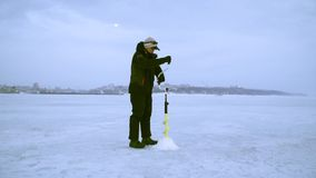 En fiskare borrar ett hål med en is borrar i vinter på i natur lager videofilmer