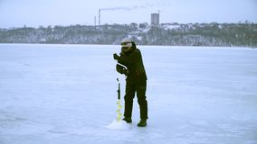 En fiskare borrar ett hål med en is borrar in vinter i staden arkivfilmer