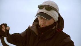 En fiskare försöker att borra ett hål för att fånga en fisk stock video