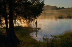 En fiskare på en skogsbevuxen sjö i dimman royaltyfri fotografi
