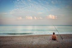 En fiskare på stranden i morgonen Arkivbild