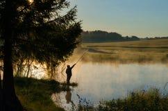 En fiskare p? en skogsbevuxen sj? i dimman royaltyfri foto