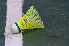 En fjäderboll som vilar på linjen av en utomhus- domstol royaltyfria bilder
