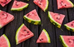 En fjärdedel av en vattenmelon på en trätabell Två vattenmelnar Sommar järtecknet Arkivfoto