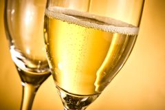 En flöjt av champagne och en som är tomma med guld- bubblor och utrymme för text Arkivfoto