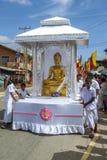En flöte som bär en guld- staty av Lord Buddha på den buddistiska peraheraprocessionen på Hikkaduwa i Sri Lanka Royaltyfria Bilder