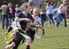 En flaggafotbolllek för 5 till 6 år - olds Arkivfoton