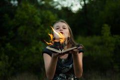 En flamma över en brandkvinna, tungor av brand Flamman täckte boken royaltyfri foto