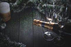 En flaska av champagne och två exponeringsglas står på ett mörkt - den gråa trätabellen som omges av julpynt arkivbilder