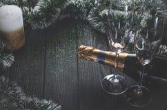 En flaska av champagne och två exponeringsglas står på ett mörkt - den gråa trätabellen som omges av julpynt och enguld royaltyfria bilder