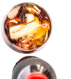 En flaska av Coladrinken med is II Royaltyfria Bilder