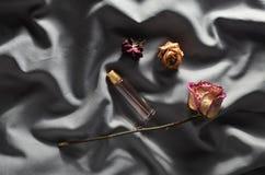 En flaska av doft och knoppar av torkade rosor på en grå siden- bakgrund Romantisk look Top beskådar arkivfoton