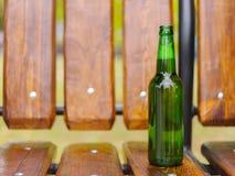 En flaska av grönt öl står på en bänk i gatan Arkivfoton