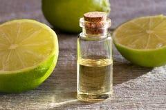 En flaska av nödvändig olja för limefrukt med nya limefrukter royaltyfria bilder