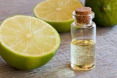 En flaska av nödvändig olja för limefrukt med nya limefrukter Fotografering för Bildbyråer