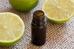 En flaska av nödvändig olja för limefrukt med nya limefrukter royaltyfri bild