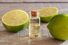 En flaska av nödvändig olja för limefrukt med nya limefrukter arkivfoton