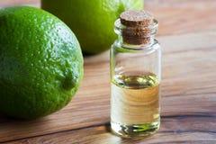 En flaska av nödvändig olja för limefrukt med nya limefrukter i backgrounen arkivbilder