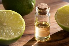 En flaska av nödvändig olja för limefrukt med nya limefrukter på en trätabl royaltyfri foto