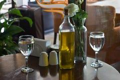 En flaska av olivolja på tabellen Två exponeringsglas av bevattnar Vas w Royaltyfri Foto
