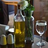 En flaska av olivolja på tabellen Två exponeringsglas av bevattnar Vas w Arkivbilder