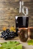 En flaska av rött vin nära druvor och ett keramiskt rånar på trälantlig bakgrund royaltyfri foto