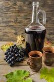 En flaska av rött vin nära druvor och ett keramiskt rånar på trälantlig bakgrund royaltyfria bilder
