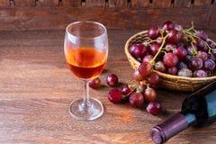 En flaska av rött vin och ett exponeringsglas av rött vin med röda druvor in arkivfoto